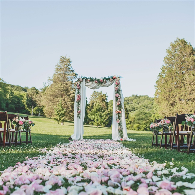 Loose petals in white and light pink formed the ceremony aisle leading up to the ceremony arch lined with a peony and rose garland.