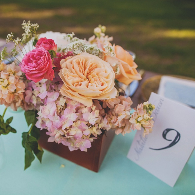 Soft, pastel colored peonies, hydrangeas and Queen Anne's lace filled wooden centerpiece boxes along with vibrant pink roses.