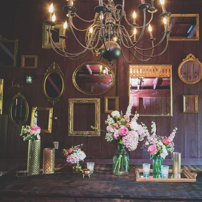 The reception was housed in a rustic barn location accented with golden frames, mirrors, chandeliers and vases.