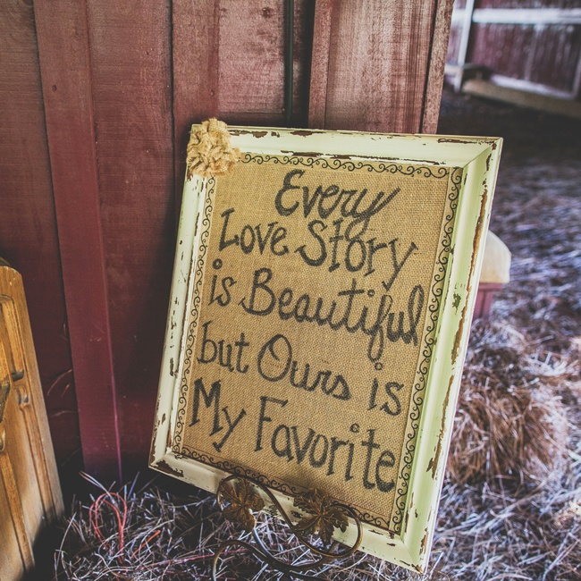 "A sign written on burlap said, ""Every love story is beautiful, but ours is my favorite,"" and was displayed in the reception area."