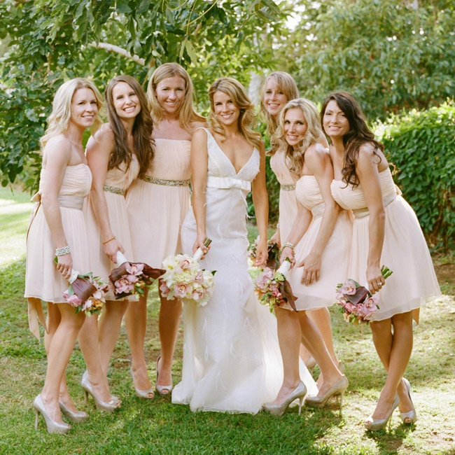 Attendants paired soft peach strapless dresses from Donna Morgan with sashes from BHLDN and subtle metallic peep-toe heels.