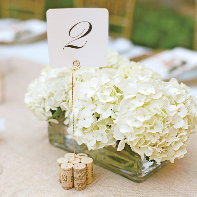 White hydrangeas in rectangular glass boxes made for a refined low centerpiece, while table names were held up with golden rods and placed in a group of wine corks.