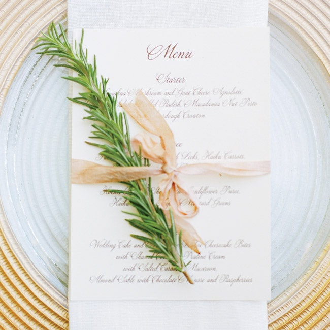 A sophisticated menu card tied up with a sprig of rosemary sat atop gold chargers for a simple, yet elegant place setting.