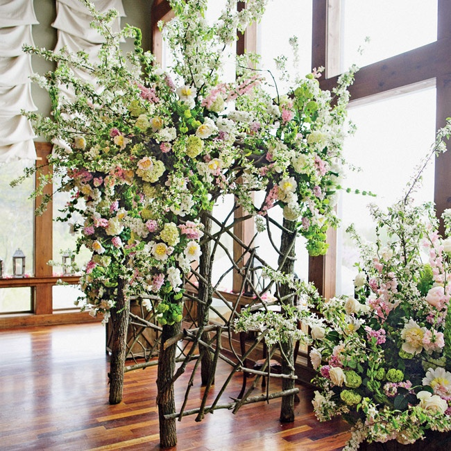 Lanier and Scott exchanged vows beneath a custom floral arch made with tree branches, and lush pink, white and green blooms.