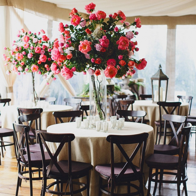 Tall glass cylinder vases housed tree branches and enormous bouquets of pink cabbage roses.