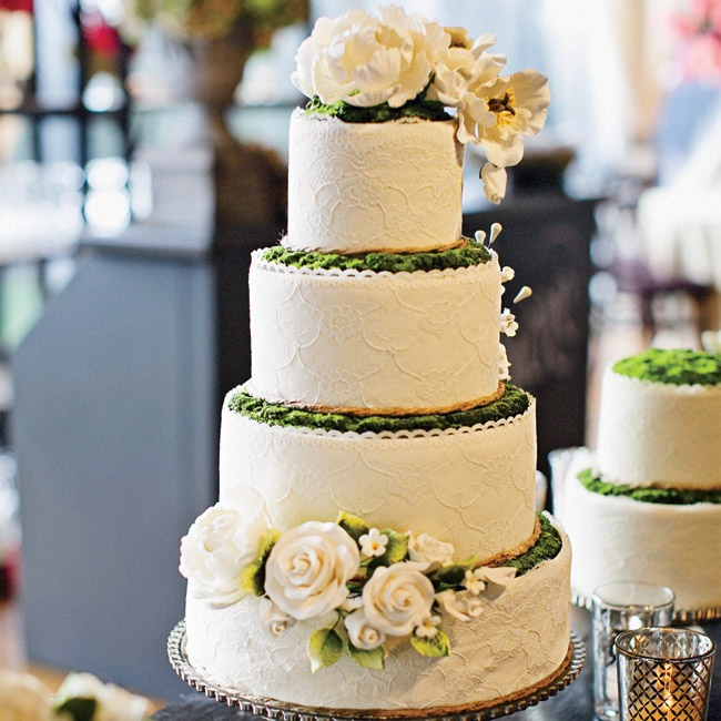The centerpiece of the dessert table was an elegant white lace four-tiered cake, lined with edible moss and topped with flowers.