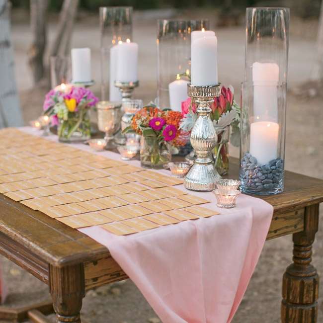 Gold escort cards were tucked into gold envelopes and displayed on a table. Anja's stylist topped the table with a pretty linen, lots of candles and flowers.