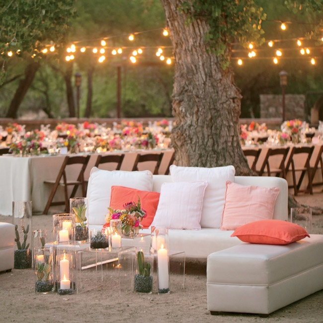Set just beyond the dinner table and in front of the outdoor dance floor was this modern white lounge. Clear coffee tables filled with candles and cactus pulled in the desert setting and created a chic place for guests to relax.