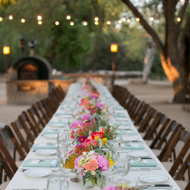 Three long tables decorated with long ivory linens and brown chairs created a formal, romantic feeling in the reception space. The florist created low centerpieces with clusters of bright flowers in pinks and oranges and objects found in the desert -- including  cholla branches, air plants and succulents.