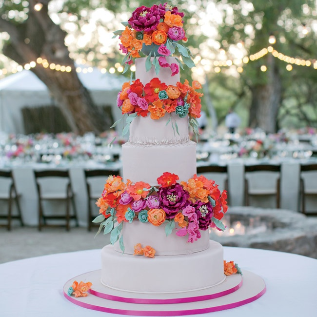 Inspired by the wedding invitations, the couple's five-tiered ivory wedding cake was decorated with bright pink and orange flowers and desert plants all made out of sugar! The topper was a little turquoise sugar-made bowl with more sugar flowers to top it off. For a meaningful final touch, each tier was lined with piping that mimicked the engraving ...