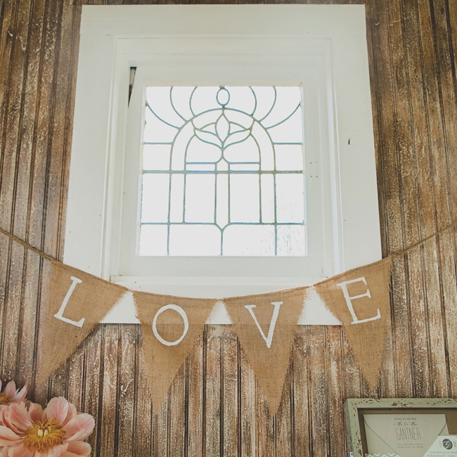 "This cute painted DIY sign spells out ""Love"" and hung above the couple's dessert spread."