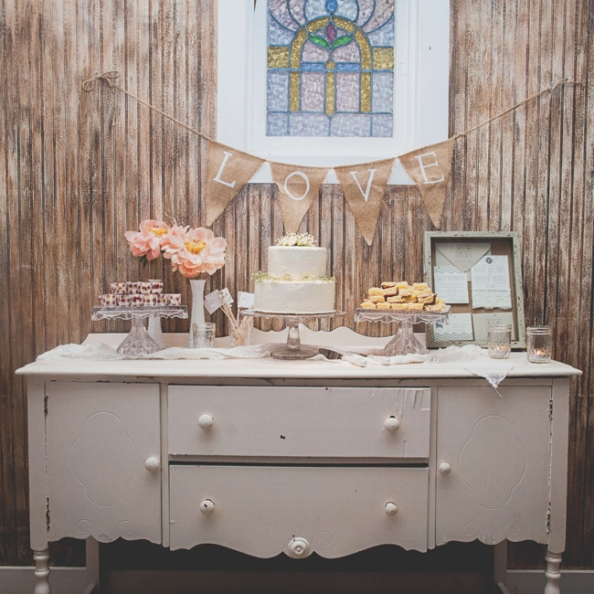 A dessert table with the couple's two-tiered white, round cake was displayed on top of an antique white dresser.