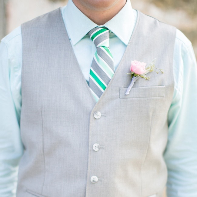 A small pink rose boutonniere was tied off with pale purple string.