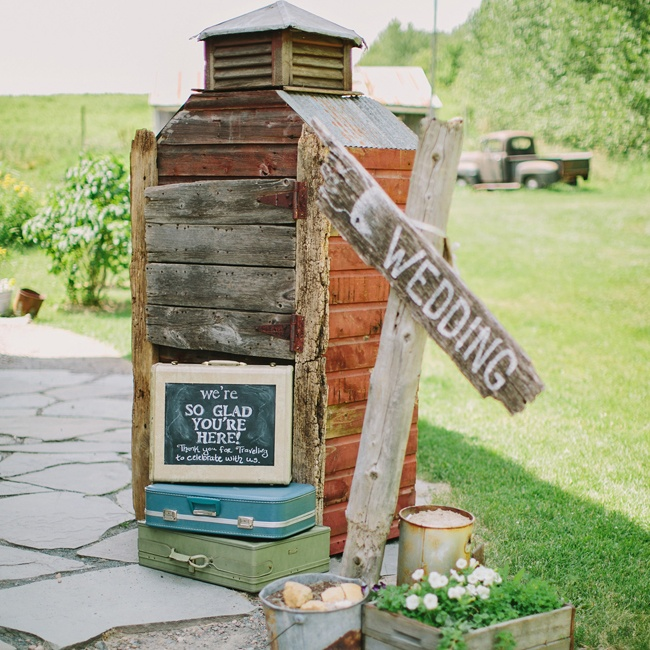 Guests were welcomed to the wedding with this painted DIY wooden sign and a few antique suitcases.