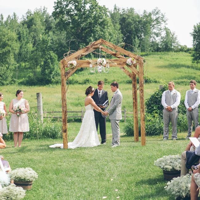 Mallory and Matt exchanged vows under a rustic wooden ceremony structure complete with a hanging chandelier and decorative vines.