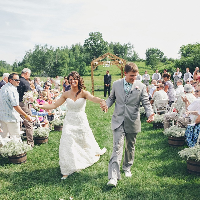 The outdoor ceremony aisle was lined with planters of baby's breath when the couple made their happy exit as newlyweds.