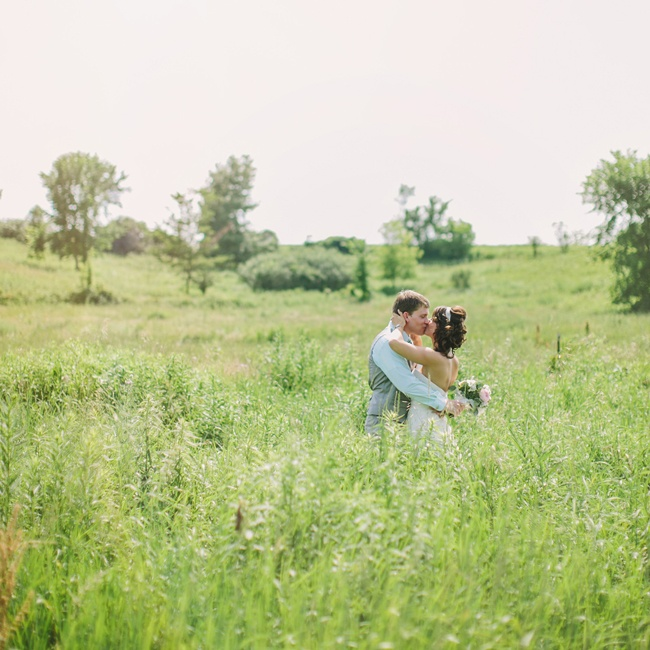 The couple exchanged their first kiss as newlyweds in the prairie grass near their reception site.