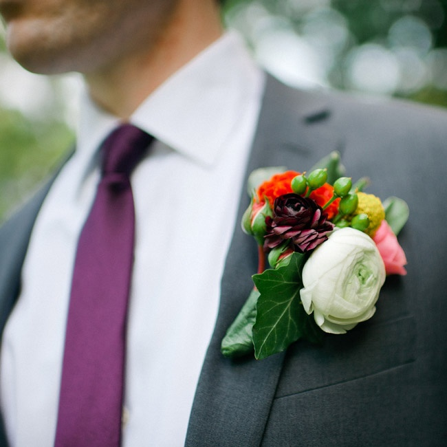 Groomsmen wore colorful and textured boutonnieres featuring billy balls and ranunculus florals.