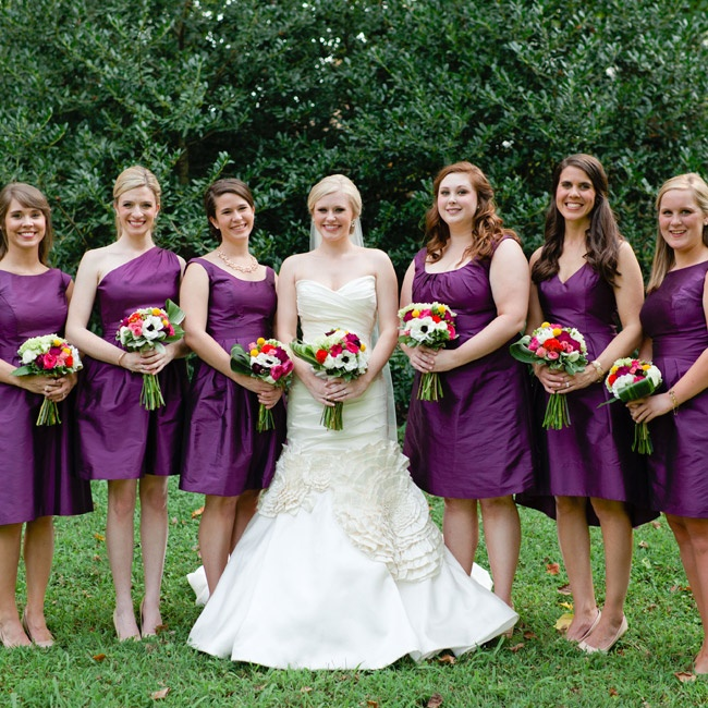 Bridesmaids wore matching amethyst gowns with different necklines by Alfred Sung. The bride wore a modern mermaid cut dress with floral ruffles by Lazaro from Bella Couture.