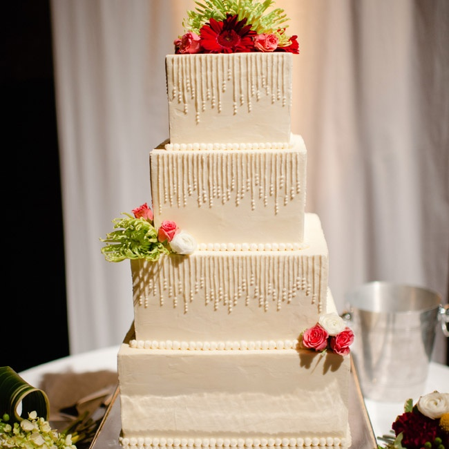 The four-tiered white modern cake was topped with fresh flowers.