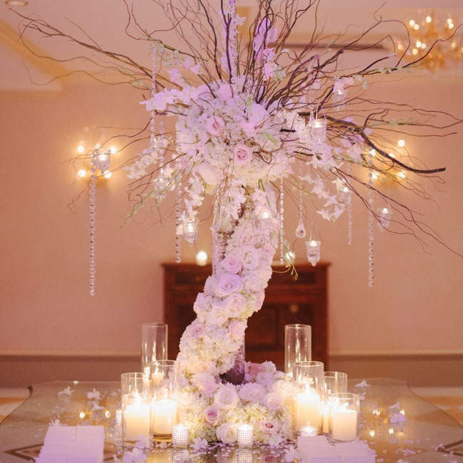 The statement arrangements of soft pale roses cascading from branches dripping with crystals and candles set a sophisticated tone for the formal reception.