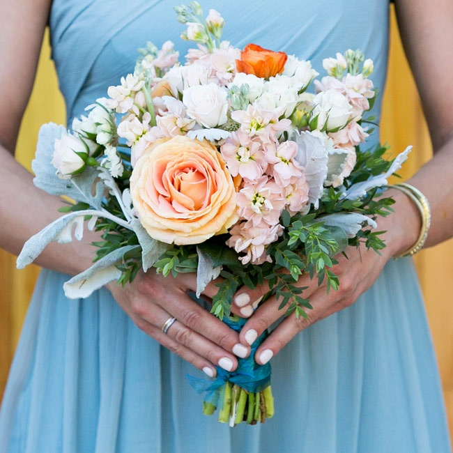 Mallie's bridesmaids carried a mix of bright peach roses and pastel blossoms which complemented their pastel blue bridesmaid dresses.