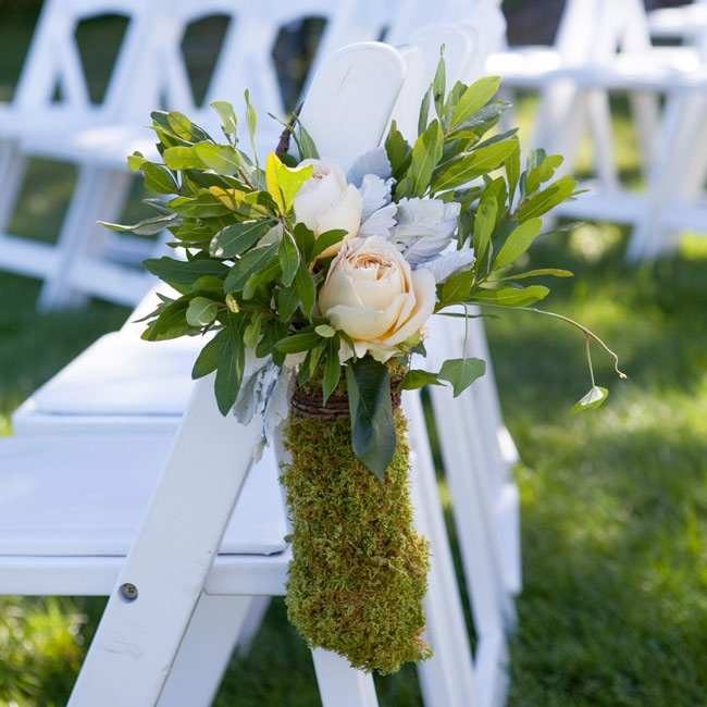 Lush green arrangements with pastel roses, dusty miller and moss marked the aisles during the ceremony.