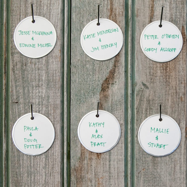 The couple created escort cards using gift tags, handwritten with green ink, and hung them on reclaimed wood.