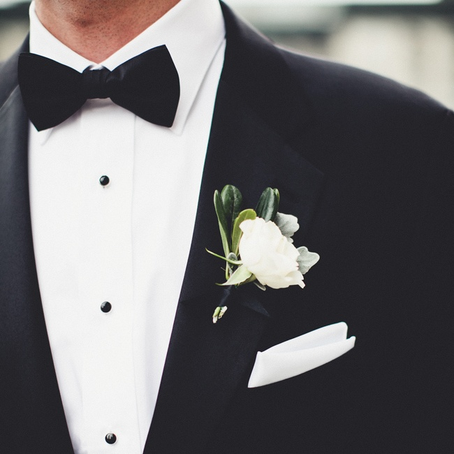 The groom wore a delicate white single flower boutonniere over his white pocket square.