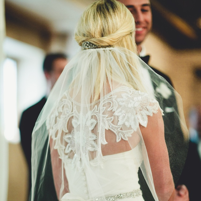 The bride wore a short white veil and a lace cover-up by Ivy & Aster over her strapless dress.