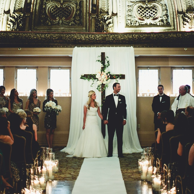 The groom custom made the ceremony cross, while the pillar candles and glass vases that lined the aisle were rented from Rented Elegance and Design in Seattle, WA.