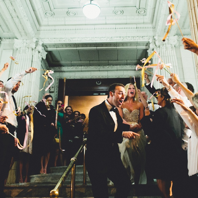 Family and friends waved streamers energetically as the bride and groom made their reception exit.