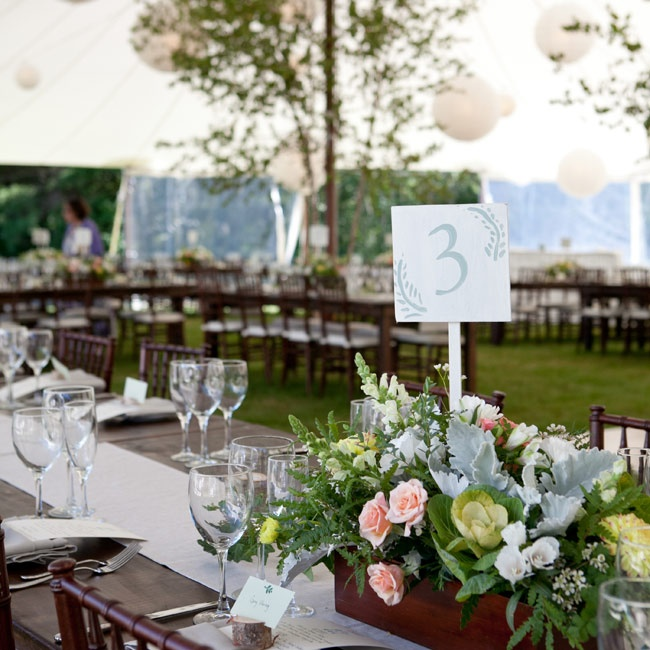 Mallie and Stuart held their reception outside under a tent decorated with large white Chinese lanterns. Trees and a grass floor gave the event a natural feel that tied in with the day's overall rustic New England feel.