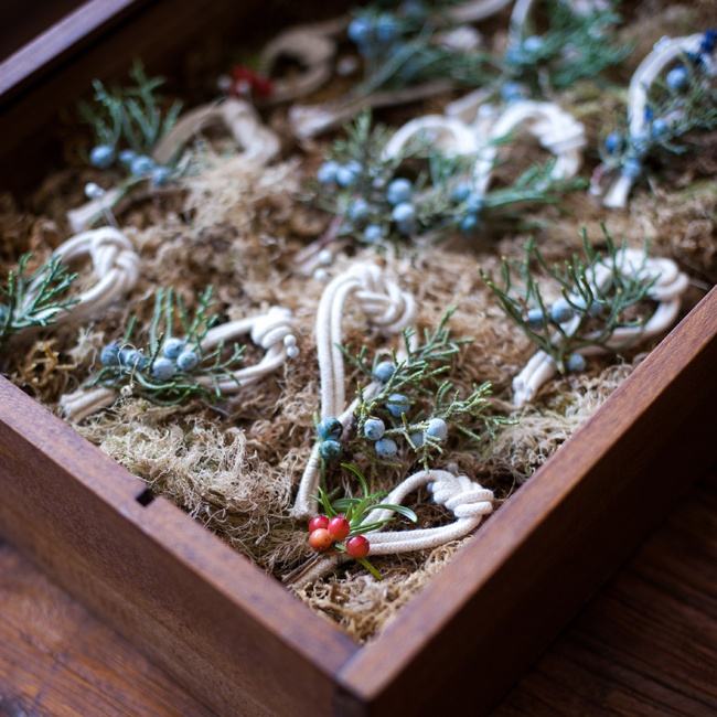 Sprigs of pine and juniper berries were tied off with a knotted rope to wear as boutonnieres.