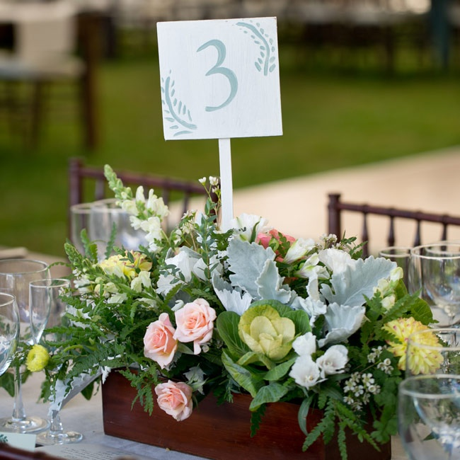 Tables were decorated with centerpieces set in dark wooden planter boxes and filled with pale pink roses, yellow dahlias, dusty miller, ferns and white snapdragons. Table cards were handmade by the bride.