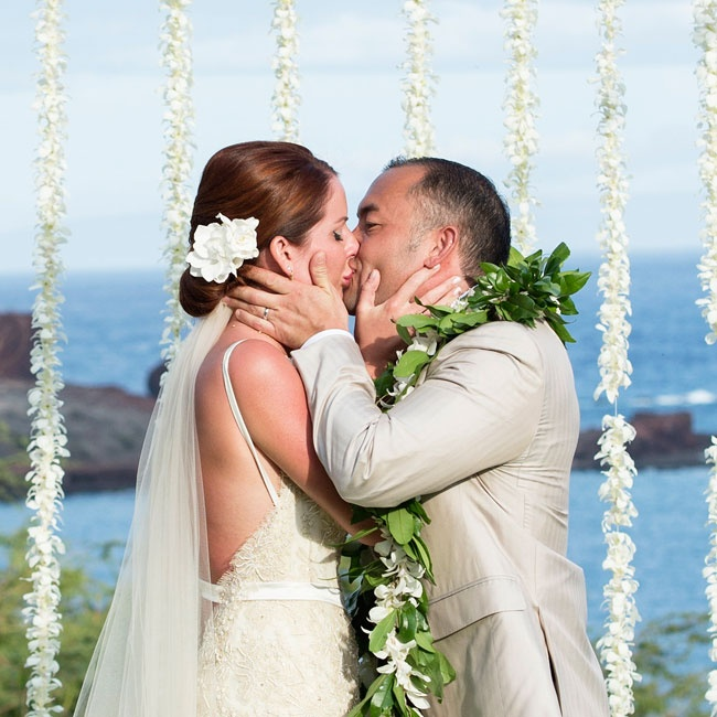 In traditional Hawaiian style, the bride and groom strung up leis of orchids for their ceremony decorations.