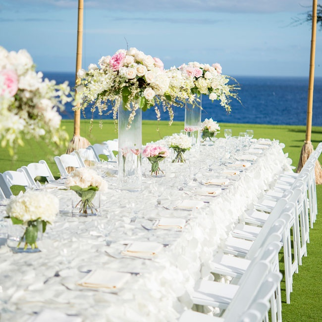 The long table alternated with low and high centerpieces filled with white and light pink flowers.