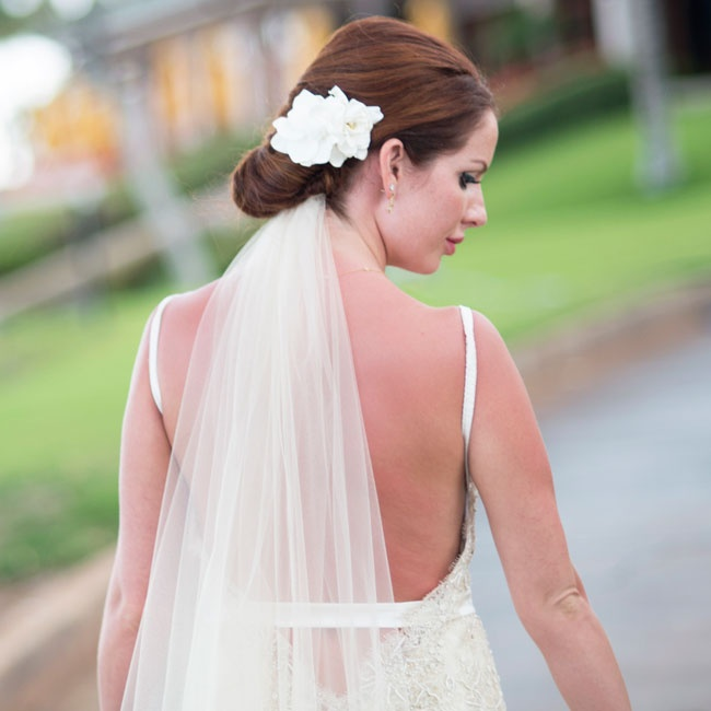 Jessica wore a low chignon updo garnished with white orchids and an ivory veil.