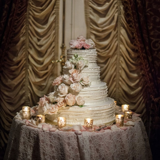 Glowing gold candles illuminated the stunning ruffled buttercream cake with cascading fresh flowers.