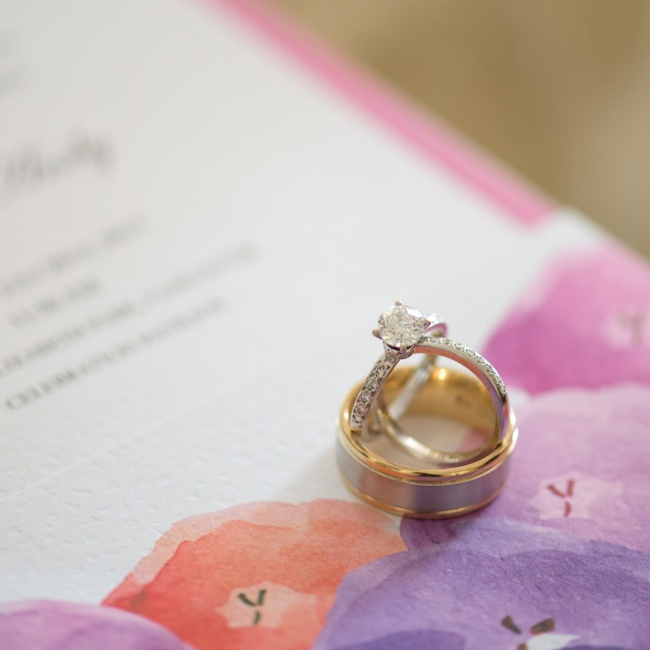 The bride and groom's rings were traditional, gold bands. Here they are pictured sitting on top of the couple's watercolor invitation suite that pulled their color palette together.