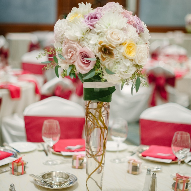 Roses, peonies and hydrangeas in light pinks, yellows and white filled tall centerpieces at the wedding reception.