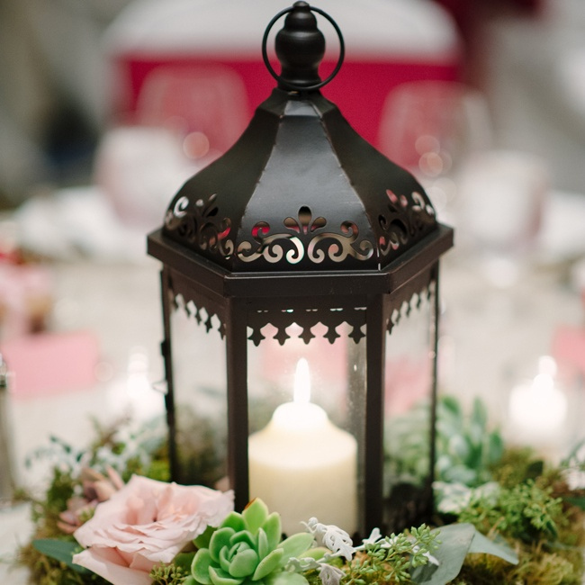Romantic candle lanterns were surrounded by green and light pink wreaths of roses and succulents.