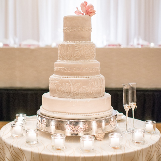 This traditional white five-tiered wedding cake's frosting design was inspired by bridal gown lace and beading.