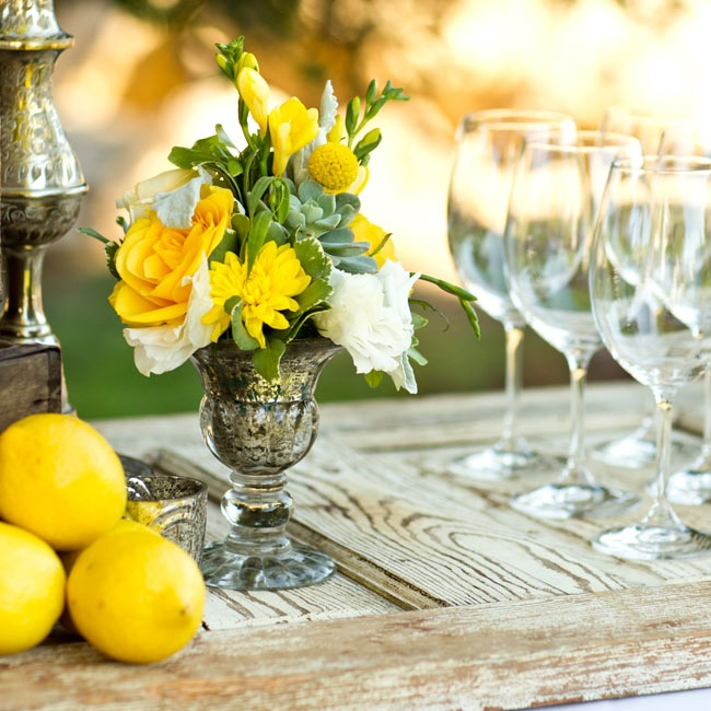 Bright yellow blooms in antique silver vases served as the centerpieces for the couple's reception. Lemons accented the tables adding a fun and rustic touch.