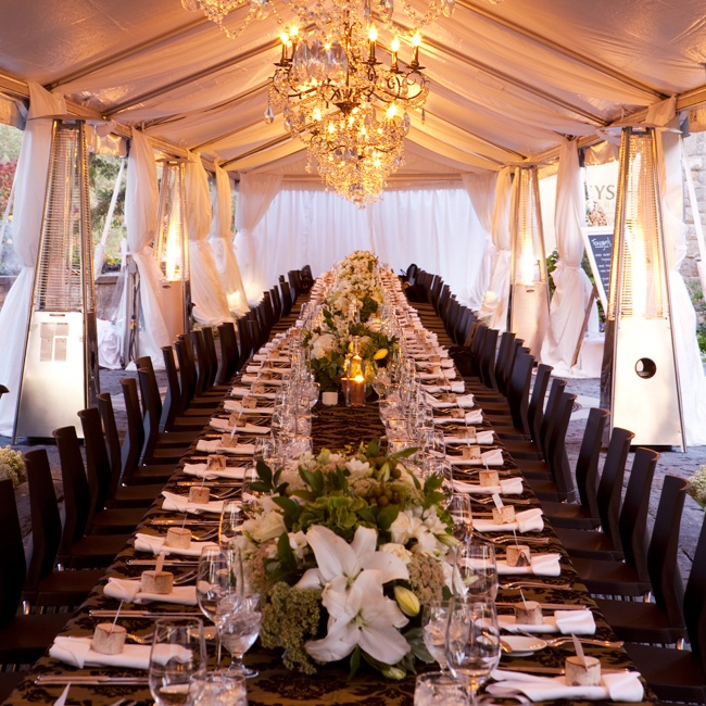 The elegant tented reception dinner featured one long table with black wooden chairs and hanging crystal chandeliers.