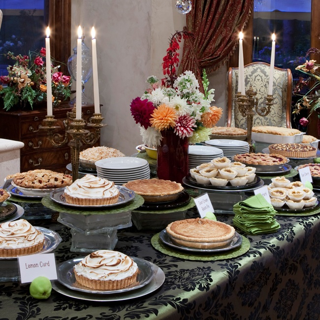 Various pies and tarts were displayed on a green and black brocade tablecloth set with candelabras.