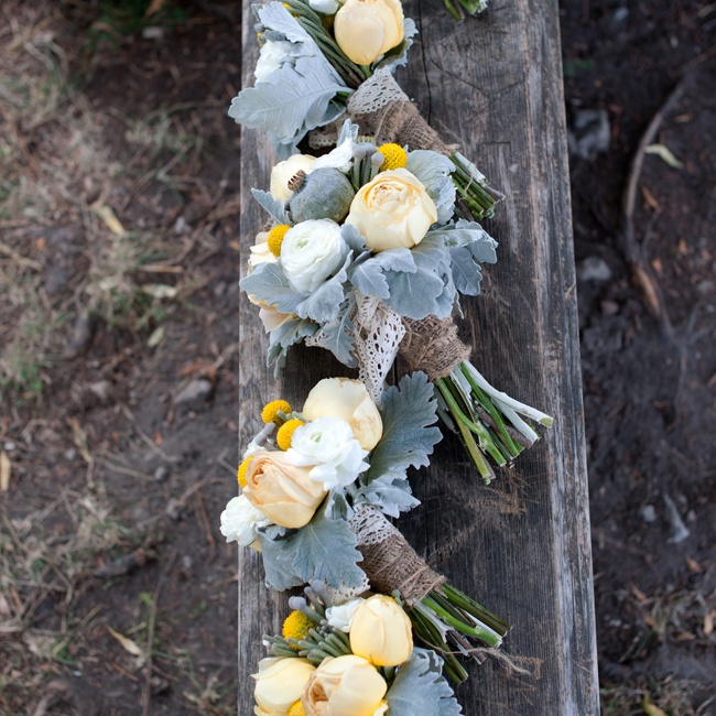The bridal and bridesmaid bouquets featured light yellow roses, bright yellow billy balls, and muted green poppy pods and dusty miller leaves. They were tied off with burlap and lace.