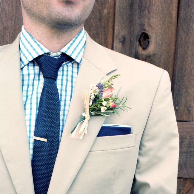 A rustic wildflower boutonniere accented the groom's blue tie and pocket square.