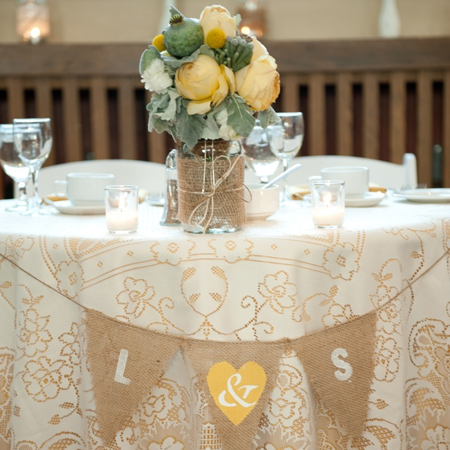 Tables were set with embroidered white and tan tablecloths. Burlap flags with the bride and groom's initials added an extra homespun element while huge rose and peony blooms and poppy pods made for interesting centerpieces.