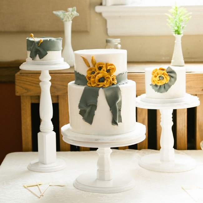 Simple white cakes with yellow and slate country details were set up on white wooden cake stands.
